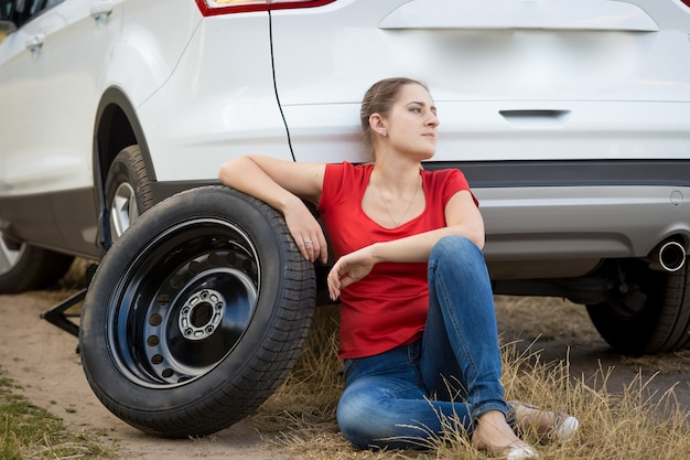 Young upset woman sitting on ground at broken car