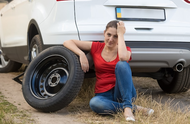 Young upset woman sitting on ground next to the spare tire