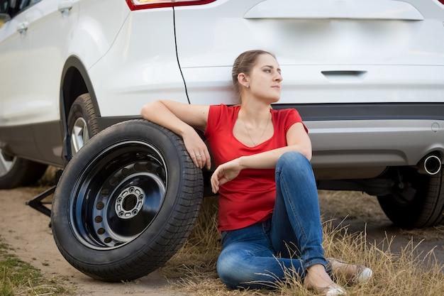 깨진 된 자동차에서 바닥에 앉아 젊은 화가 여자
