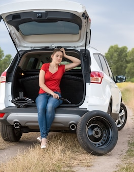 開いた車のトランクに座って、タイヤを交換する助けを待っている若い動揺の女性