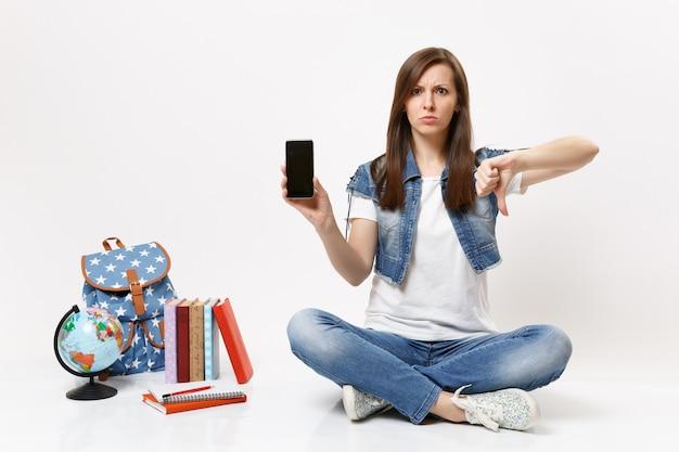 Молодая расстроенная студентка держит мобильный телефон с пустым черным пустым экраном, показывая большой палец вниз возле школьных учебников рюкзака глобуса