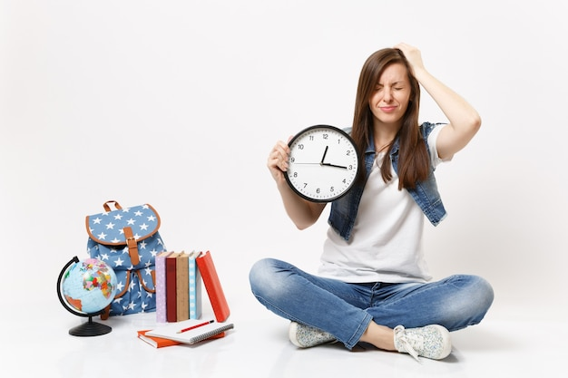 Giovane studentessa sconvolta con gli occhi chiusi che tiene la sveglia aggrappata alla testa seduta vicino al globo, zaino, libri di scuola isolati