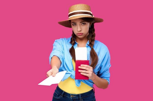Молодой расстроенный турист женщины с паспортом давая билет на самолет. кавказский путешественник в летней повседневной одежде в розовом изолированном фоне. студентка с документом