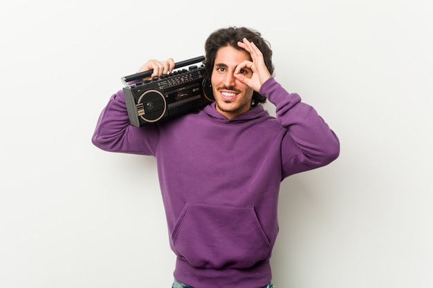 Young urban man holding a guetto blaster excited keeping ok gesture on eye.