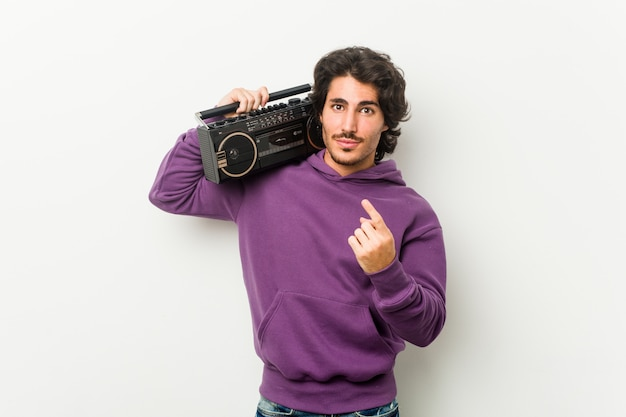 Young urban man holding a guetto blaster pointing with finger at you as if inviting come closer.