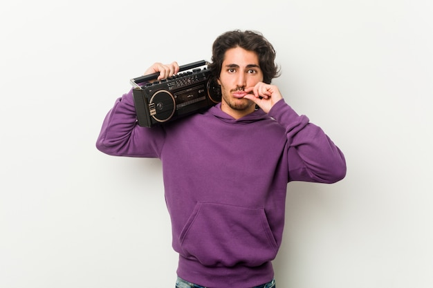 Young urban man holding a guetto blaster with fingers on lips keeping a secret.