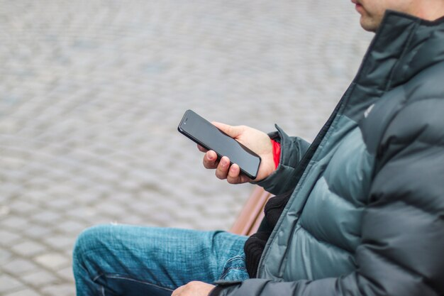 Young urban man using a smartphone sitting on a bench in a city street.