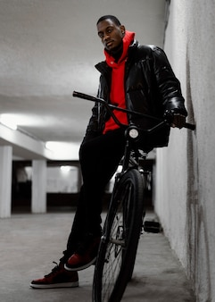 Young urban man walking with his bike