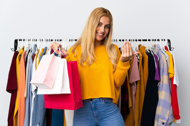 Young uruguayan blonde woman in a clothing store and holding shopping bags inviting to come with hand.