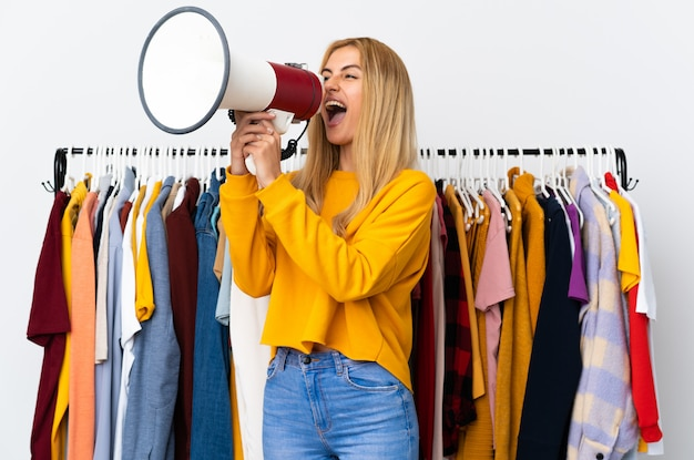 Young uruguayan blonde woman in a clothing store shouting through a megaphone