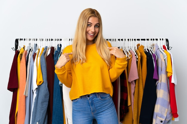 Young uruguayan blonde woman in a clothing store with surprise facial expression