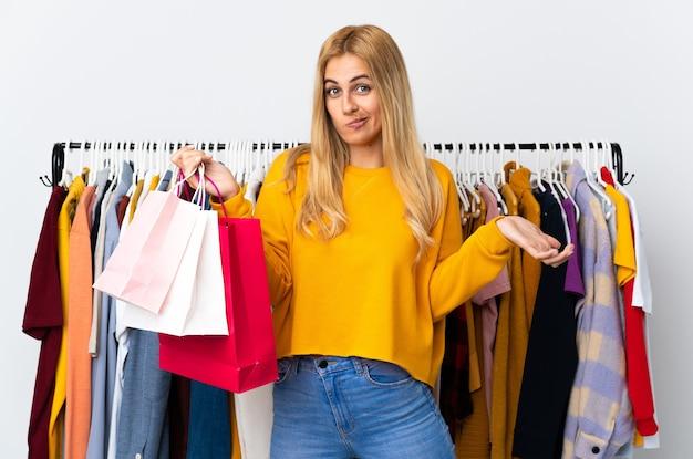 Молодая уругвайская блондинка в магазине одежды и держит сумки с покупками, делая жест сомнения, поднимая плечи