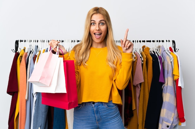Молодая уругвайская блондинка в магазине одежды держит сумки с покупками, указывая на отличную идею
