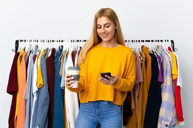 Молодая уругвайская блондинка в магазине одежды держит кофе на вынос и на мобильный