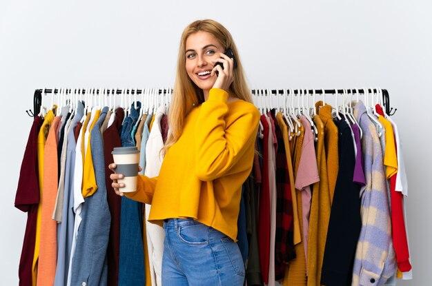 持ち帰り用のコーヒーと携帯電話を持っている衣料品店の若いウルグアイのブロンドの女性