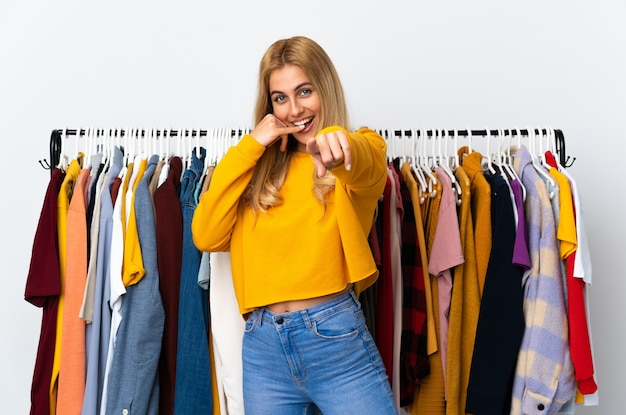 電話ジェスチャーをして正面を向いている衣料品店の若いウルグアイのブロンドの女性