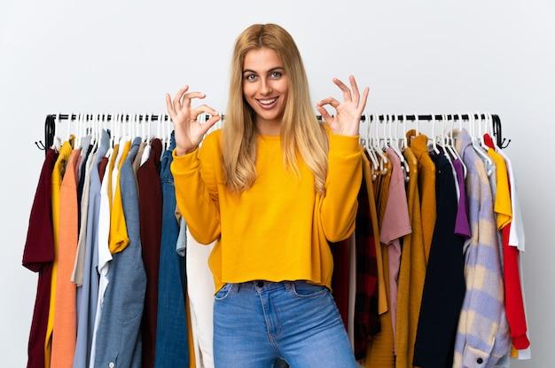 指でokの標識を示す衣料品店で若いウルグアイのブロンドの女性