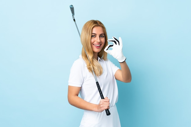 Young uruguayan blonde woman over isolated blue playing golf making ok sign
