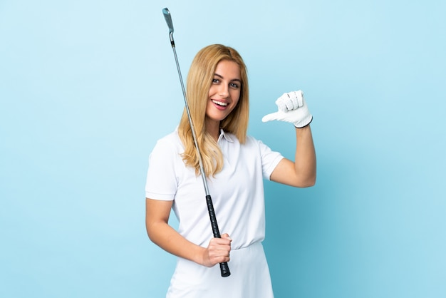 Young uruguayan blonde woman over isolated blue wall playing golf and proud of himself