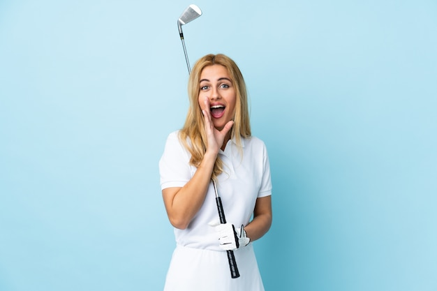 Young uruguayan blonde woman over isolated blue wall playing golf and shouting with mouth wide open