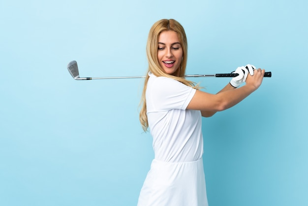 Young uruguayan blonde woman over isolated blue wall playing golf