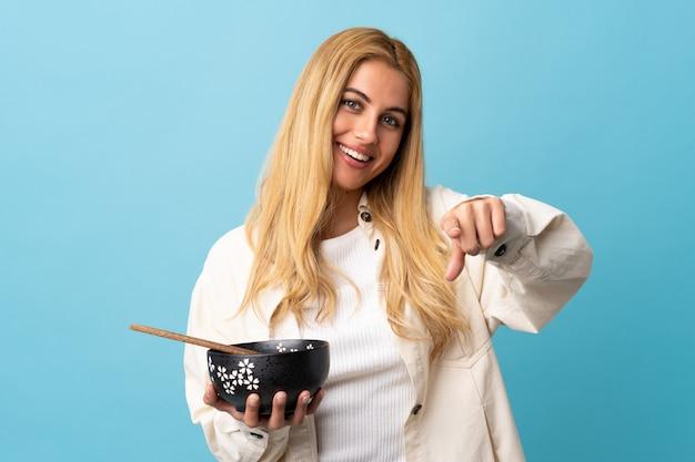 Молодая уругвайская белокурая женщина над синей стеной уверенно показывает на тебя пальцем, держа миску лапши с палочками для еды