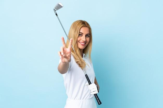 골프를하고 승리 기호를 보여주는 격리 된 파란색 벽 위에 젊은 우루과이 금발 여자