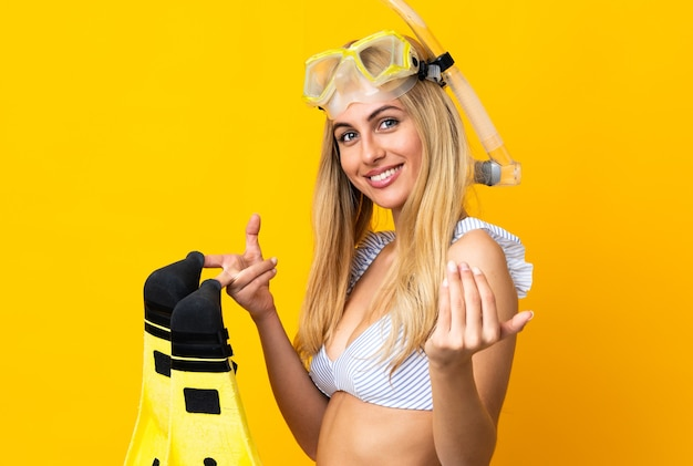 Young uruguayan blonde woman in swimsuit holding fins and diving goggles in summer holidays inviting to come with hand. happy that you came