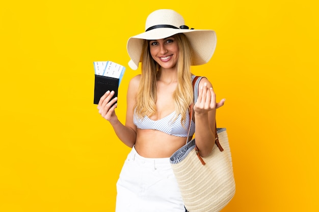 Young uruguayan blonde woman in swimsuit holding a passport over isolated yellow background inviting to come with hand. happy that you came