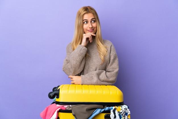 疑問と考えを持つ孤立した紫の壁に服の完全なスーツケースを持つ若いウルグアイブロンドの女性