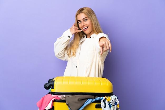 電話ジェスチャーを作ると前を指している孤立した紫の壁に服の完全なスーツケースを持つ若いウルグアイブロンドの女性
