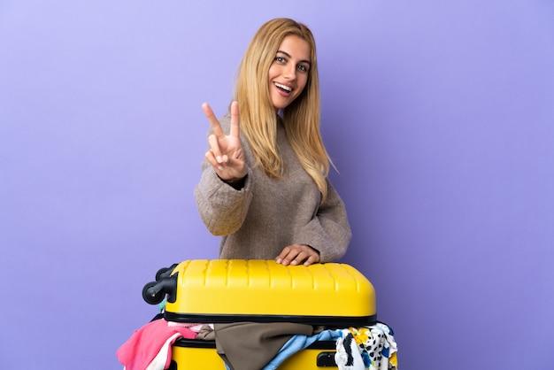 笑顔と勝利のサインを示す分離の紫の壁に服の完全なスーツケースを持つ若いウルグアイブロンドの女性