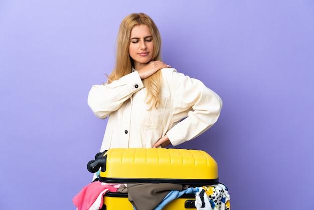 Молодая уругвайская белокурая женщина с чемоданом, полным одежды над изолированной фиолетовой стеной, страдающей от боли в плече за приложенное усилие