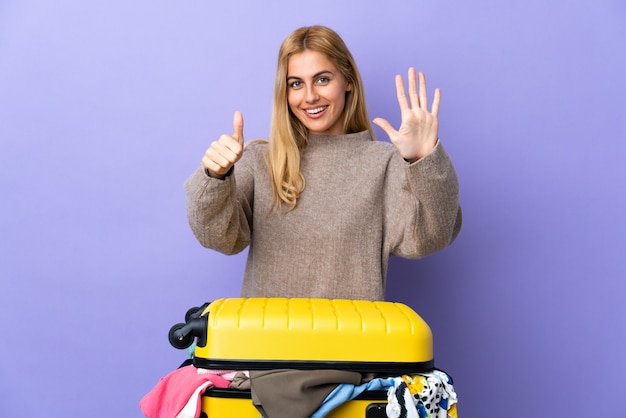 Young uruguayan blonde woman with a suitcase full of clothes over isolated purple wall counting six with fingers