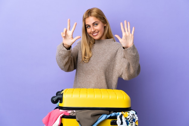 Young uruguayan blonde woman with a suitcase full of clothes over purple wall counting eight with fingers