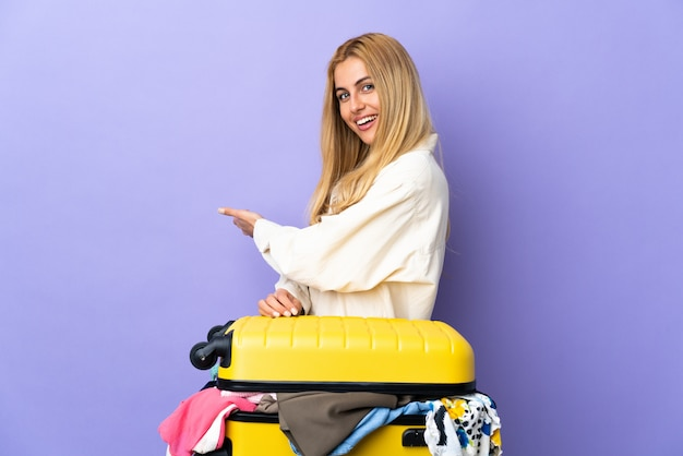 Young uruguayan blonde woman with a suitcase full of clothes over purple wall extending hands to the side for inviting to come