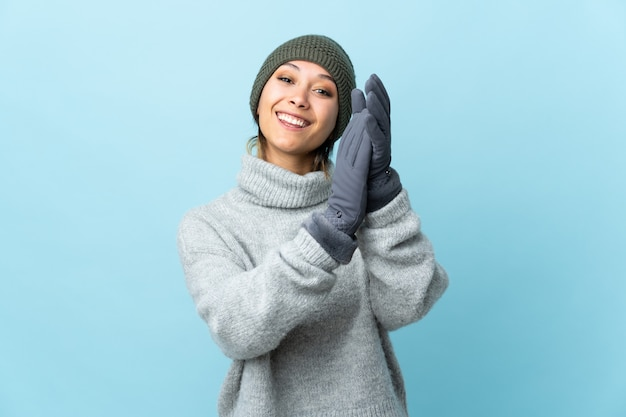 Young uruguayan girl with winter hat on blue wall applauding