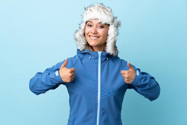 Young uruguayan girl with winter hat on blue wall giving a thumbs up gesture