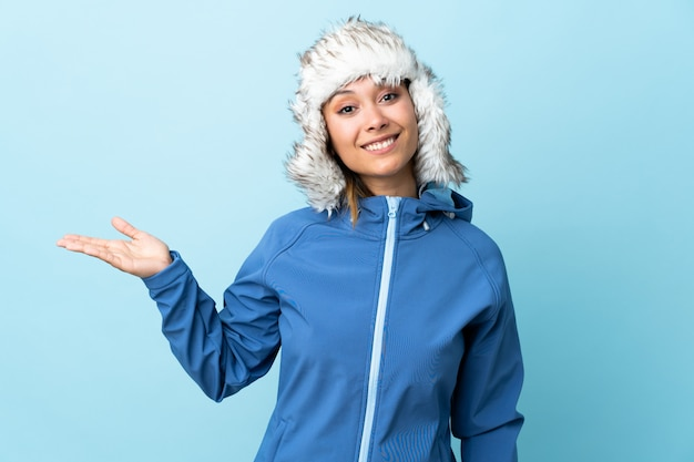 Young uruguayan girl with winter hat isolated on blue background holding copyspace imaginary on the palm