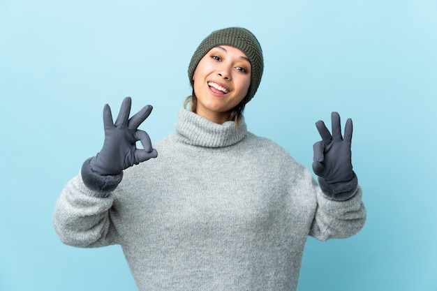 Young uruguayan girl with winter hat isolated on blue background showing an ok sign with fingers