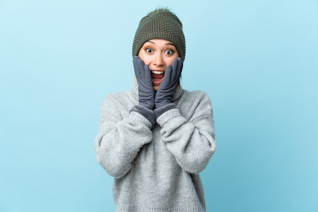 Young uruguayan girl with winter hat isolated on blue background with surprise facial expression