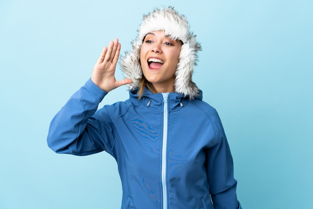 Young uruguayan girl with winter hat isolated on blue shouting with mouth wide open
