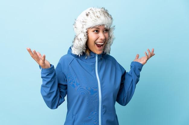 驚きの表情で青い背景に分離された冬の帽子を持つウルグアイ少女