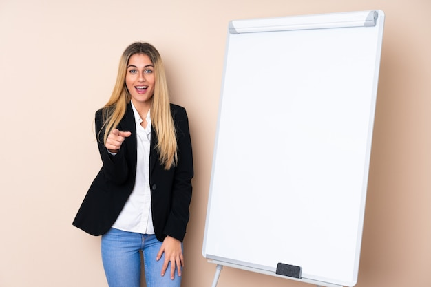 Young uruguayan woman giving a presentation on white board and surprised while pointing front