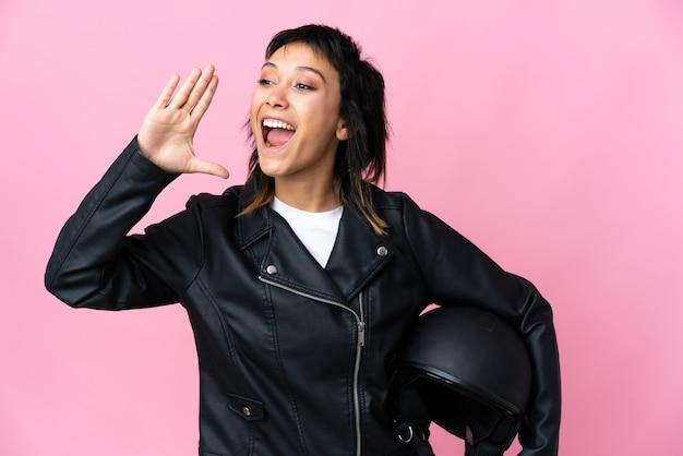 Молодая уругвайская женщина, держащая мотоциклетный шлем, изолировала розовую стену, крича с широко открытым ртом