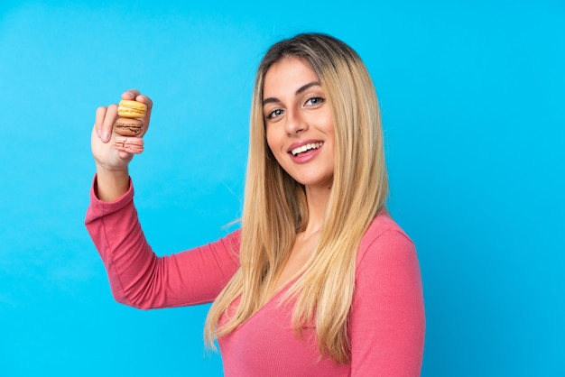 Young uruguayan woman over isolated blue wall holding colorful french macarons and smiling a lot