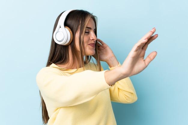 Молодая уругвайская женщина изолирована на синем, слушает музыку и танцует