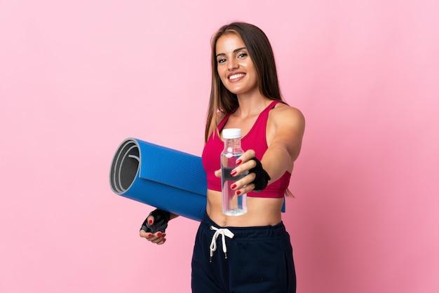 Молодая уругвайская женщина изолирована на розовой стене со спортивной бутылкой с водой и с циновкой