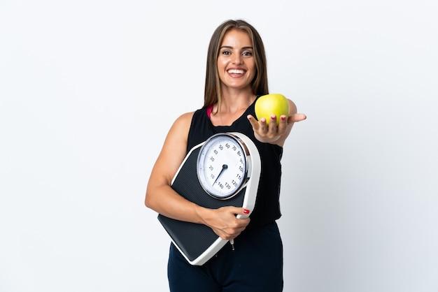 무게 기계를 들고 사과를 제공하는 흰색 배경에 고립 된 젊은 우루과이 여자