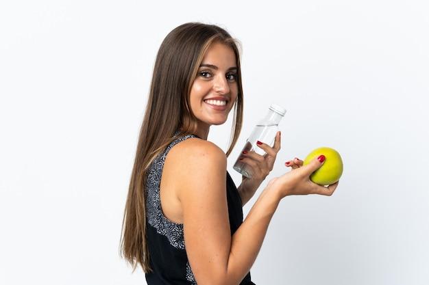 リンゴと水のボトルで白い背景で隔離の若いウルグアイの女性